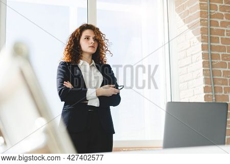 Portrait Of A Beautiful Successful Young Business Woman With Red Curly Hair In The Office Interior S