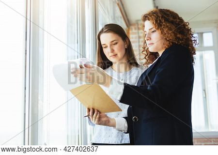 A Beautiful Young Brunette Woman And A Red-haired Woman Are Talking And Discussing Working Moments N