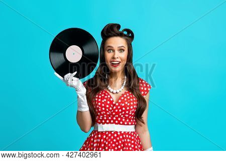 Happy Pinup Woman In Retro Dress Holding Gramophone Vinyl Record, Smiling And Looking At Camera Over