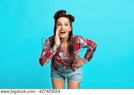 Sexy Young Pinup Woman Shouting, Making Announcement, Holding Hand Near Mouth Over Blue Studio Backg