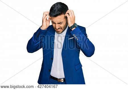 Young hispanic man wearing business jacket suffering from headache desperate and stressed because pain and migraine. hands on head.