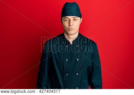Handsome young man wearing professional cook uniform and hat depressed and worry for distress, crying angry and afraid. sad expression.