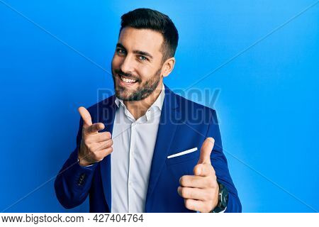 Young hispanic businessman wearing business jacket pointing fingers to camera with happy and funny face. good energy and vibes.