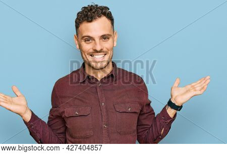 Young hispanic man wearing casual clothes smiling showing both hands open palms, presenting and advertising comparison and balance