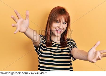 Redhead young woman wearing casual striped t shirt looking at the camera smiling with open arms for hug. cheerful expression embracing happiness.