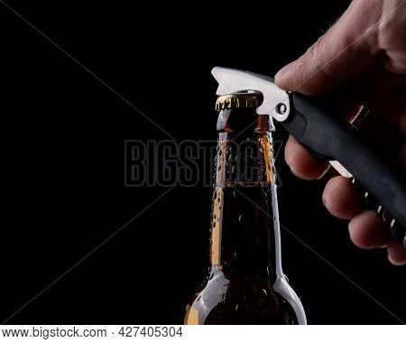 A Man Opens A Bottle Of Beer From A Dark Glass With Drops Of Condensation On A Black Background.