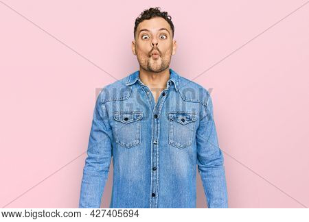 Young hispanic man wearing casual denim jacket making fish face with lips, crazy and comical gesture. funny expression.