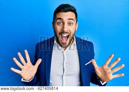 Young hispanic businessman wearing business jacket celebrating crazy and amazed for success with arms raised and open eyes screaming excited. winner concept