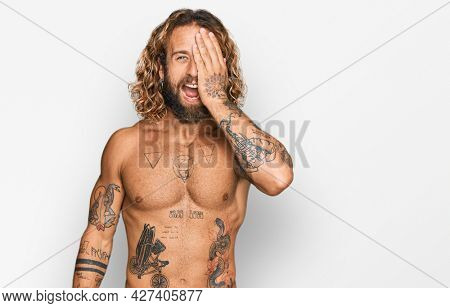 Handsome man with beard and long hair standing shirtless showing tattoos covering one eye with hand, confident smile on face and surprise emotion.