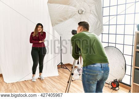 Young woman at photography studio thinking looking tired and bored with depression problems with crossed arms.