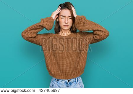 Young caucasian girl wearing casual clothes suffering from headache desperate and stressed because pain and migraine. hands on head.