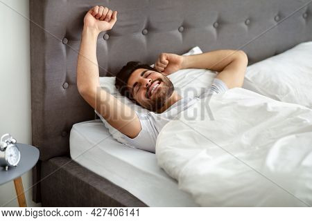 Rested Arab Man Waking Up And Stretching Hands, Wellslept Guy Lying In Bed, Awakening In Cozy Bedroo