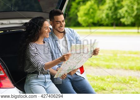 Loving Middle-eastern Couple Watching Map While Having Break, Copy Space