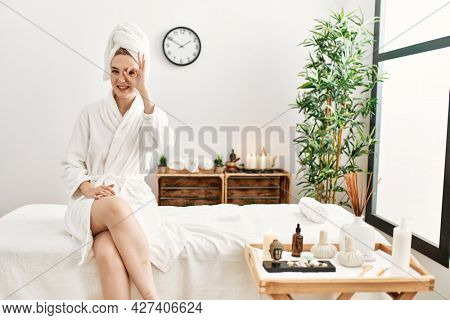 Young blonde woman wearing bathrobe at wellbeing spa doing ok gesture with hand smiling, eye looking through fingers with happy face.
