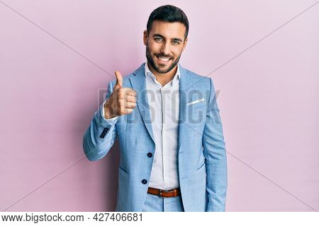Young hispanic businessman wearing business jacket doing happy thumbs up gesture with hand. approving expression looking at the camera showing success.