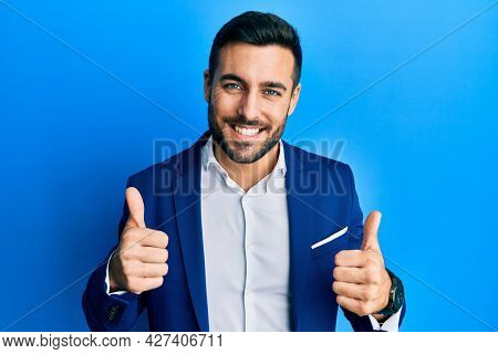 Young hispanic businessman wearing business jacket success sign doing positive gesture with hand, thumbs up smiling and happy. cheerful expression and winner gesture.
