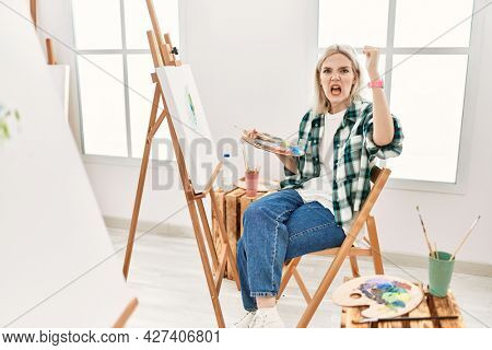 Young artist woman painting on canvas at art studio angry and mad raising fist frustrated and furious while shouting with anger. rage and aggressive concept.