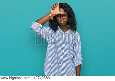 Beautiful african young woman wearing casual clothes and glasses making fun of people with fingers on forehead doing loser gesture mocking and insulting.