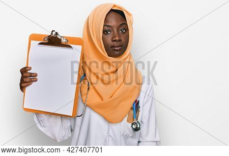 Beautiful african young woman wearing doctor stethoscope holding clipboard thinking attitude and sober expression looking self confident