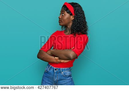 Beautiful african young woman wearing casual clothes looking to the side with arms crossed convinced and confident