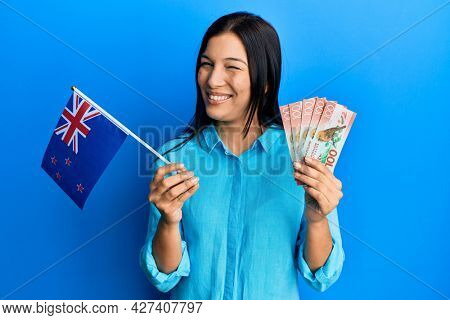 Young latin woman holding new zealand flag and dollars winking looking at the camera with sexy expression, cheerful and happy face.