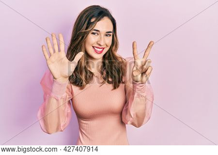 Young hispanic girl wearing casual clothes showing and pointing up with fingers number seven while smiling confident and happy.