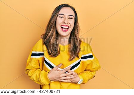 Young hispanic girl wearing casual clothes smiling and laughing hard out loud because funny crazy joke with hands on body.