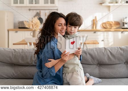 Excited Mom Enjoy Reading Birthday Wishes In Postcard From Small Son. Happy Young Mum Embrace Presch