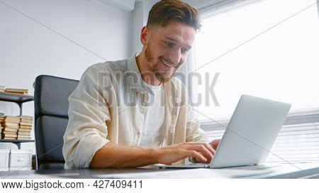 Freelancer professional bank analyst prepares contract online typing on laptop sitting at table with sheets of papers at home