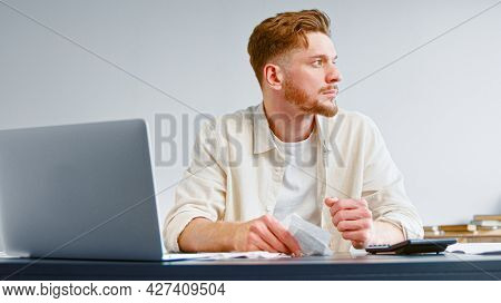 Bearded company analyst in analyzes sums in paper invoice receipts and becomes upset at table with calculator and laptop in room