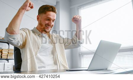 Concentrated businessman signs contract online and raises hands with happiness sitting near white laptop at grey office table