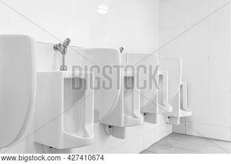 Row Of White Ceramic Urinals In The Men's Bathroom