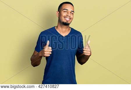 Young african american man wearing casual t shirt success sign doing positive gesture with hand, thumbs up smiling and happy. cheerful expression and winner gesture.