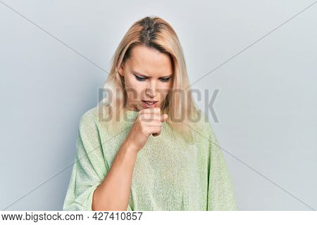 Beautiful caucasian blonde woman wearing casual winter sweater feeling unwell and coughing as symptom for cold or bronchitis. health care concept.
