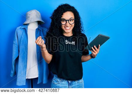 Young hispanic woman with curly hair wearing staff t shirt holding touchpad device screaming proud, celebrating victory and success very excited with raised arm