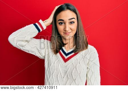 Young brunette girl wearing casual student sweater confuse and wonder about question. uncertain with doubt, thinking with hand on head. pensive concept.
