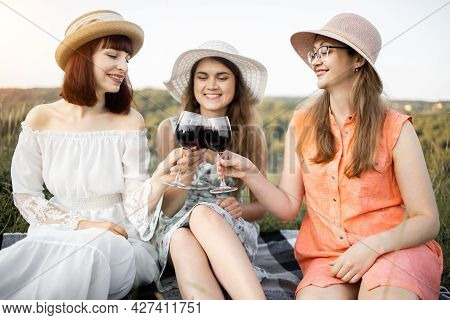 Hen Party. Girls Frienship And Fun. Group Of Three Young Women In Hats And Dresses, Enjoying Tasty F