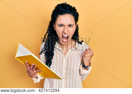 Young hispanic woman with curly hair holding book angry and mad raising fist frustrated and furious while shouting with anger. rage and aggressive concept.