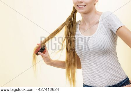 Blonde Girl With Brush Combing Her Long Hair. Girl Taking Care Refreshing Her Hairstyle. Haircare Co