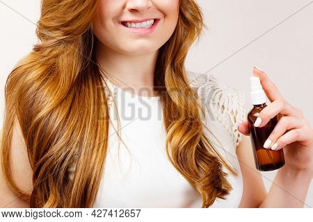 Female Model With Shiny Wavy Brown Long Hair Using Cosmetic, Thermal Protect Spray. Treatment With O