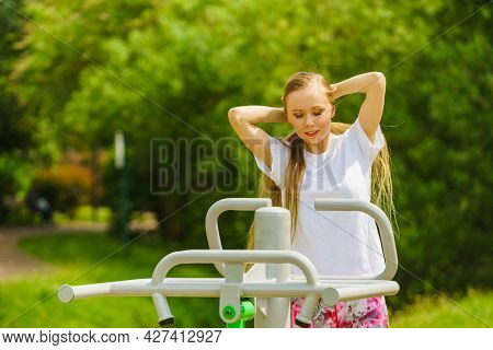Young Woman Working Out Outside. Girl Making Exercises And Training On Public Equipment In Outdoor G