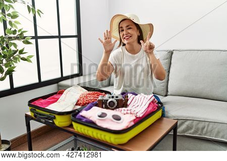 Beautiful middle age hispanic woman packing summer clothes in suitcase showing and pointing up with fingers number seven while smiling confident and happy.