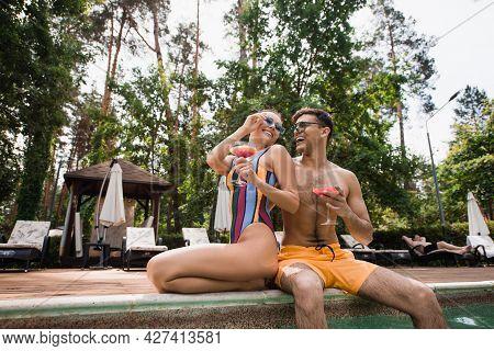 Cheerful Man In Swim Trunks Holding Cocktail Near Girlfriend On Poolside