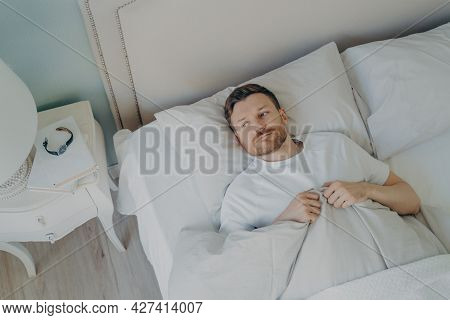 View From Above Of Stressed Young Caucasian Male Lying In Bed With His Eyes Open And Being Unable To