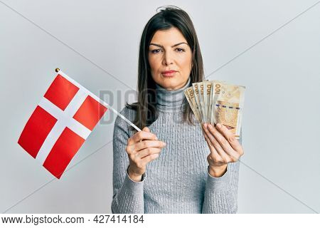 Young hispanic woman holding danmark flag and krone banknotes relaxed with serious expression on face. simple and natural looking at the camera.
