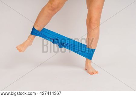 Self Determined Bodybuilder Does Exercises With Rubber Band, Works On Hands And Legs. Sport Concept.