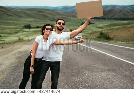 Hitchhiking Trip. A Couple Tries To Stop A Car On The Road With An Empty Cardboard Sign, A Mock-up.