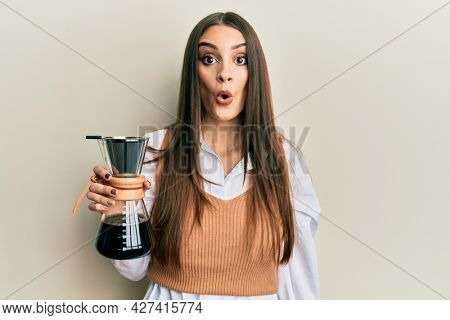 Beautiful brunette young woman holding soluble coffee maker scared and amazed with open mouth for surprise, disbelief face