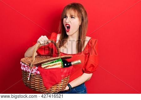 Redhead young woman holding picnic wicker basket with bread angry and mad screaming frustrated and furious, shouting with anger. rage and aggressive concept.