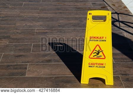 Yellow Warning Sign For Wet Floor Standing On Brown Tiled Floor. The Inscription On Yellow Informati